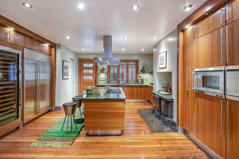 This is a charming kitchen with hardwood flooring that matches with the kitchen island and surrounding cabinetry that houses the stainless steel modern appliances. Images courtesy of Toptenrealestatedeals.com.