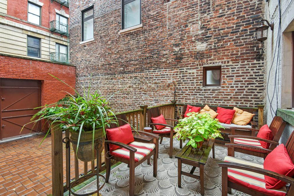 This is the beautiful and relaxing patio on a raised concrete deck with wooden railings surrounding the outdoor furniture. You can also see here the backyard parking and beautiful red brick walls. Images courtesy of Toptenrealestatedeals.com.