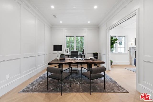 This spacious home office has a bright ceiling that illuminates the white walls with its recessed lights. This makes the black elements stand out like the swivel chair, desk and table lamp.