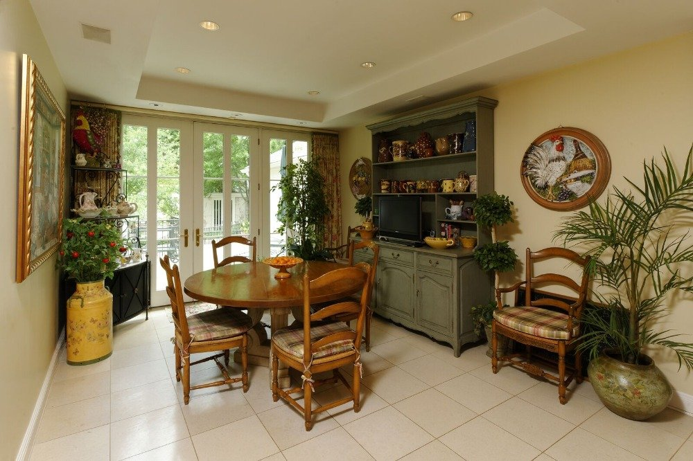 A dining nook featuring a round dining table set for four, along with a TV on the side. Images courtesy of Toptenrealestatedeals.com.