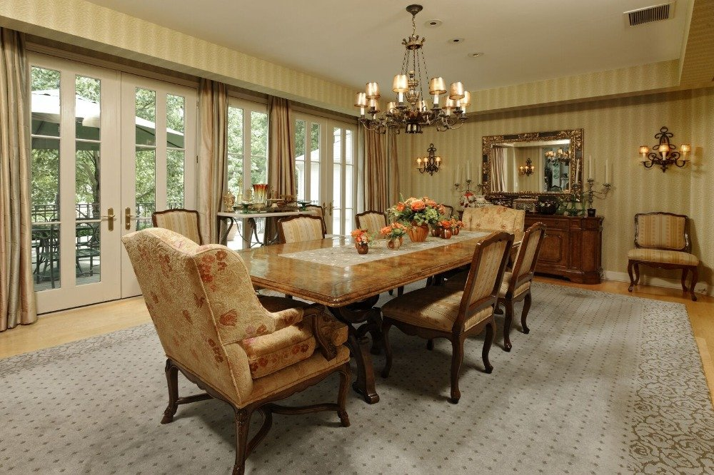 Large formal dining room boasting an elegant dinnig table and chairs set lighted by a fancy chandelier. Images courtesy of Toptenrealestatedeals.com.