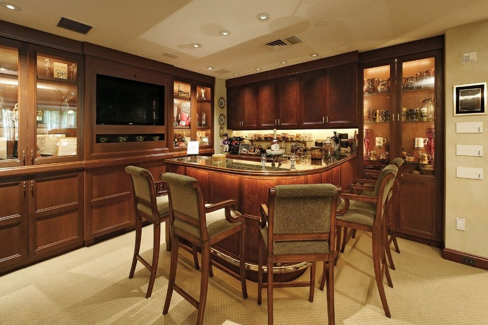 A bar area with a gorgeous bar counter with classy bar stools. There's a TV on the wall as well. Images courtesy of Toptenrealestatedeals.com.