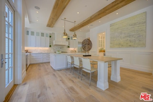 This angle of the charming kitchen has a built-in wooden table attached to its white kitchen island. This table blends quite well with the hardwood flooring and the exposed beams of the white ceiling.