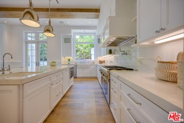 The long and narrow hardwood flooring of this kitchen pairs well with the classic white cabinetry that blend well with the white ceiling adorned with exposed beams and pendant lights.