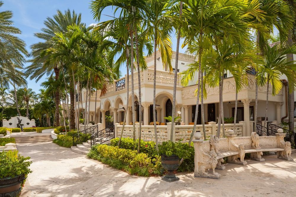 This view of the back of the house gives us a look at its gorgeous arches and balconies adorned with tall tropical trees and shrubs. Images courtesy of Toptenrealestatedeals.com.