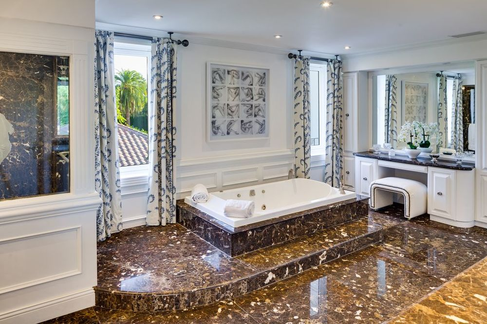 This is the primary bathroom with a large bathtub inlaid with the same brown marble tiles as the flooring. This is flanked by two windows with curtains. Images courtesy of Toptenrealestatedeals.com.