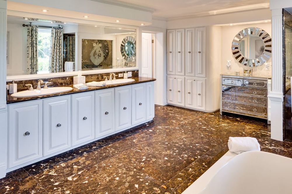 Across from the bathtub is this gorgeous vanity topped with a large mirror. The white cabinetry of this vanity matches with those built-in cabinets on the side of the door and mirrored drawers. . Images courtesy of Toptenrealestatedeals.com.