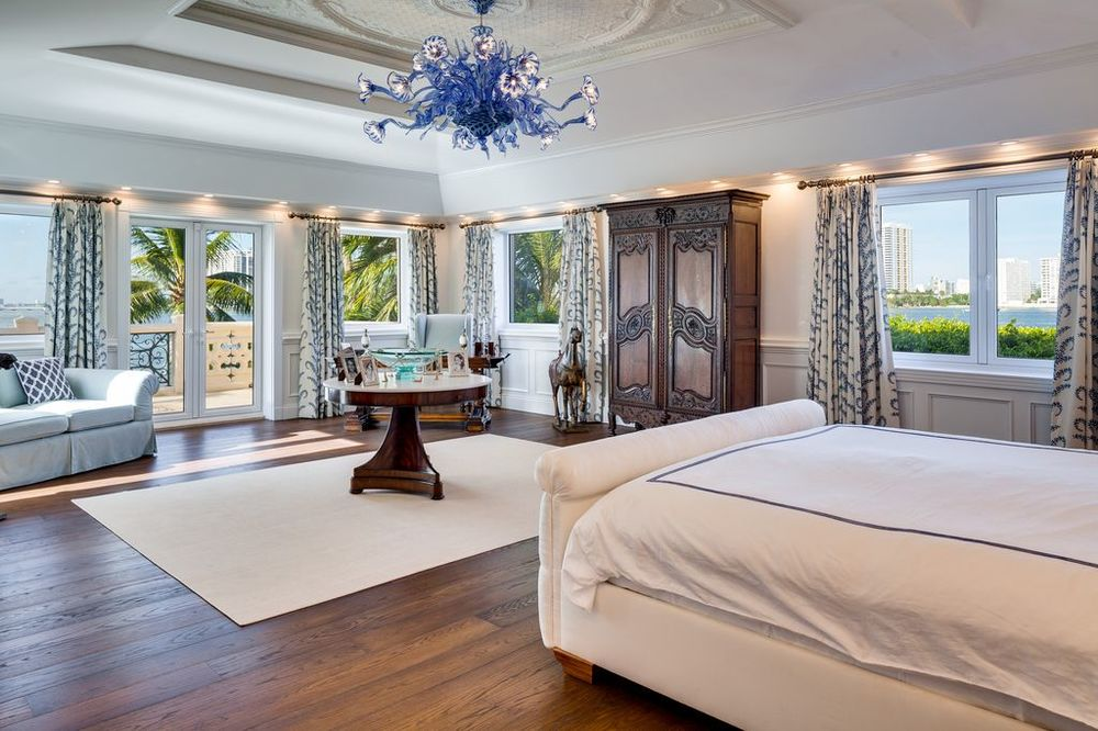 This primary bedroom has a large decorative purple chandelier in the middle of its bright tray ceiling. It has a beige cushioned sleigh bed that stand out against the dark hardwood flooring. Images courtesy of Toptenrealestatedeals.com.