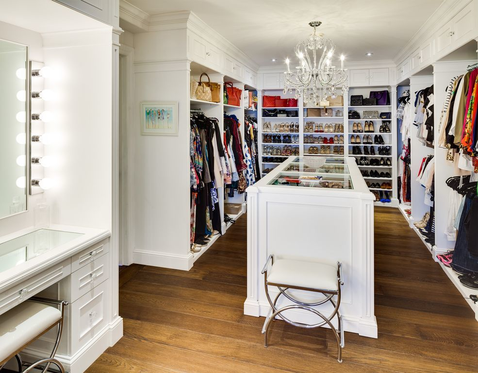 The spacious walk-in closet has enough hardwood flooring for an island in the middle of the built-in white cabinetry of shelves and racks topped with a small chandelier. Images courtesy of Toptenrealestatedeals.com.