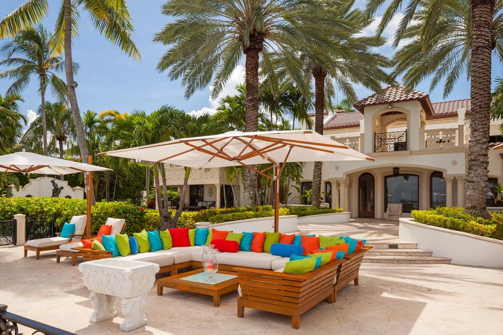 This closer look at the sitting area by the water shows a U-shaped outdoor sofa with cushions and lots of colorful pillows. Images courtesy of Toptenrealestatedeals.com.