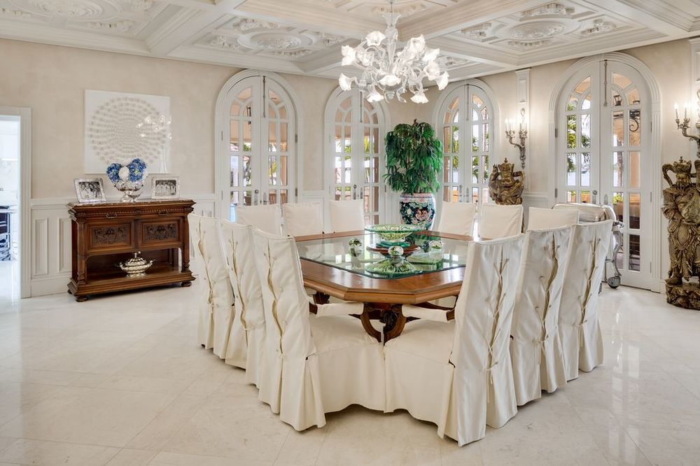 This is a sophisticated formal dining room with intricate details on its bright coffered ceiling that hangs a white chandelier over the wooden dining table and its chairs covered in slipcovers. Images courtesy of Toptenrealestatedeals.com.