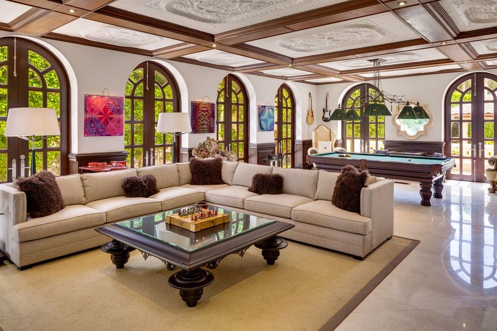 The game room has charming arched windows that provide natural lighting for the pool table and the large L-shaped sectional sofa beside it. Images courtesy of Toptenrealestatedeals.com.