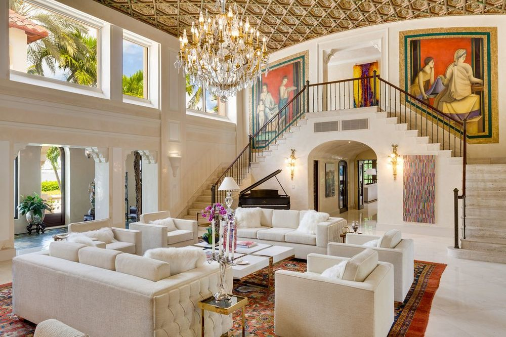 This angle of the living room shows the indoor balcony adorned with a large colorful painting. This also shows that the gold and crystal chandelier hangs over the large coffee table in between the sofa sets. Images courtesy of Toptenrealestatedeals.com.
