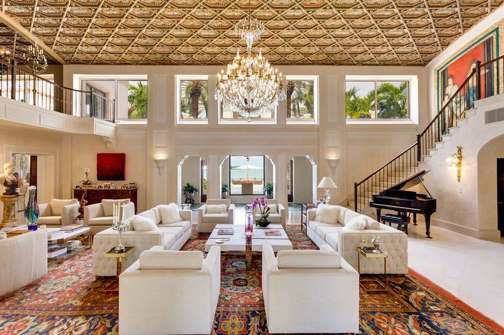 This view of the living room shows more of the soaring patterned ceiling that hangs a majestic chandelier. These are then complemented by the transom windows and arches. Images courtesy of Toptenrealestatedeals.com.