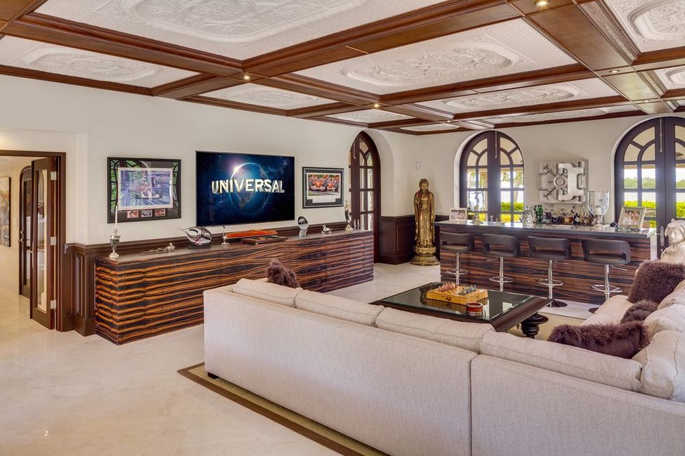 This is a spacious media room with a large gray sectional sofa topped with a coffered ceiling accented by the wooden elements. Images courtesy of Toptenrealestatedeals.com.