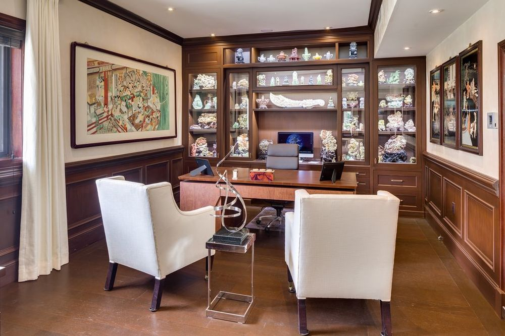 This elegant home office has a dark wooden desk that matches perfectly with the hardwood flooring, wainscoting and built in cabinetry. Images courtesy of Toptenrealestatedeals.com.