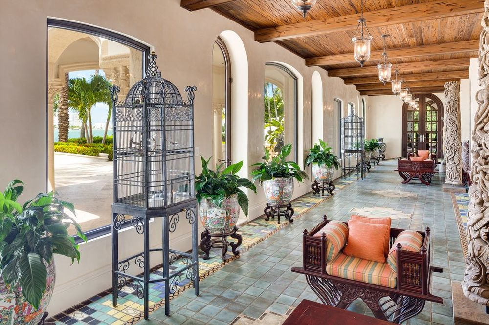 This is the covered patio with lovely woven wicker chairs with cushions standing on charming light gray tiles illuminated by arched windows. Images courtesy of Toptenrealestatedeals.com.