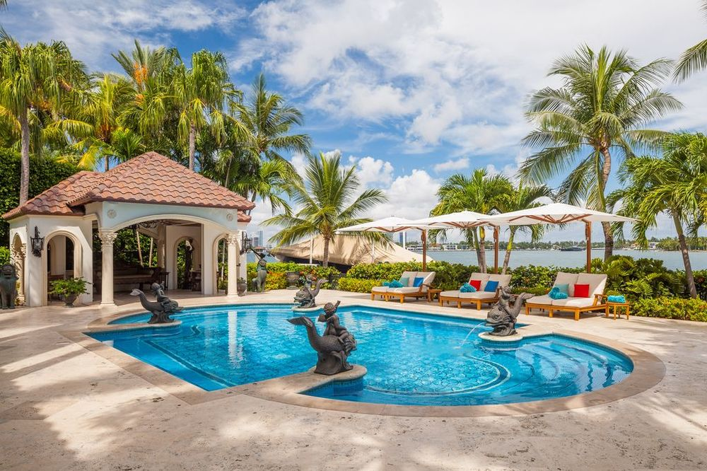 This is the gorgeous pool of the mansion with a cabana on the side along with comfortable lawn chairs with a background of tall tropical trees. Images courtesy of Toptenrealestatedeals.com.