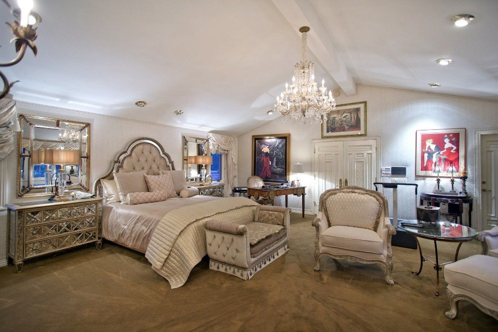This bedroom offers an elegant bed set along with a sitting area. The room also features carpeted flooring and a gorgeous chandelier ceiling light. Images courtesy of Toptenrealestatedeals.com.