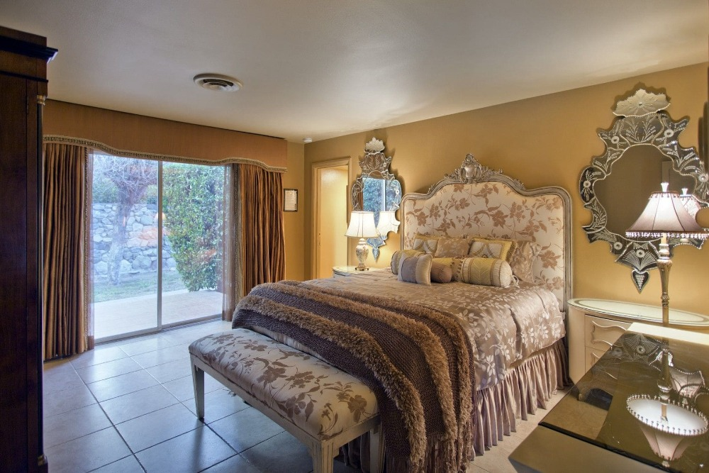 This bedroom offers a fancy bed setup lighted by table lamps on both sides. Images courtesy of Toptenrealestatedeals.com.