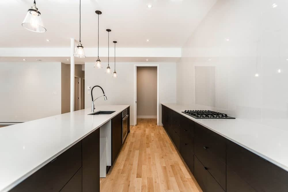 Here you can see the bright white countertops of the long and narrow kitchen contrast with the black modern cabinetry. These are then topped with pendant lights and complemented by the hardwood flooring.