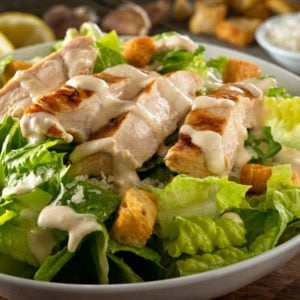 A delicious bowl of chicken ceasar salad with croutons.