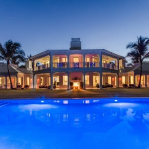 This is the back view of the house that showcases the large swimming pool that glows with its own lighting. This serves as a nice foreground for the mansion that glows warmly from its glass walls and outdoor areas. Images courtesy of Toptenrealestatedeals.com.