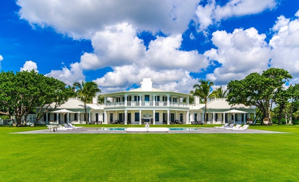 This is a view of the back of the house showcasing the bright exteriors of the mansion to be contrasted by the lush grass lawn and the flanking tall trees. Images courtesy of Toptenrealestatedeals.com.