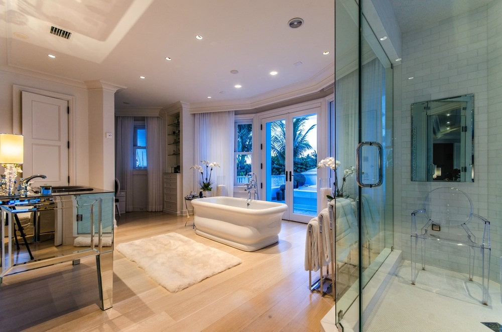 This primary bathroom has a large freestanding bathtub in the middle of its beige flooring illuminated by the tinted glass windows. On the side of this is the glass door of the walk-in shower area. Images courtesy of Toptenrealestatedeals.com.