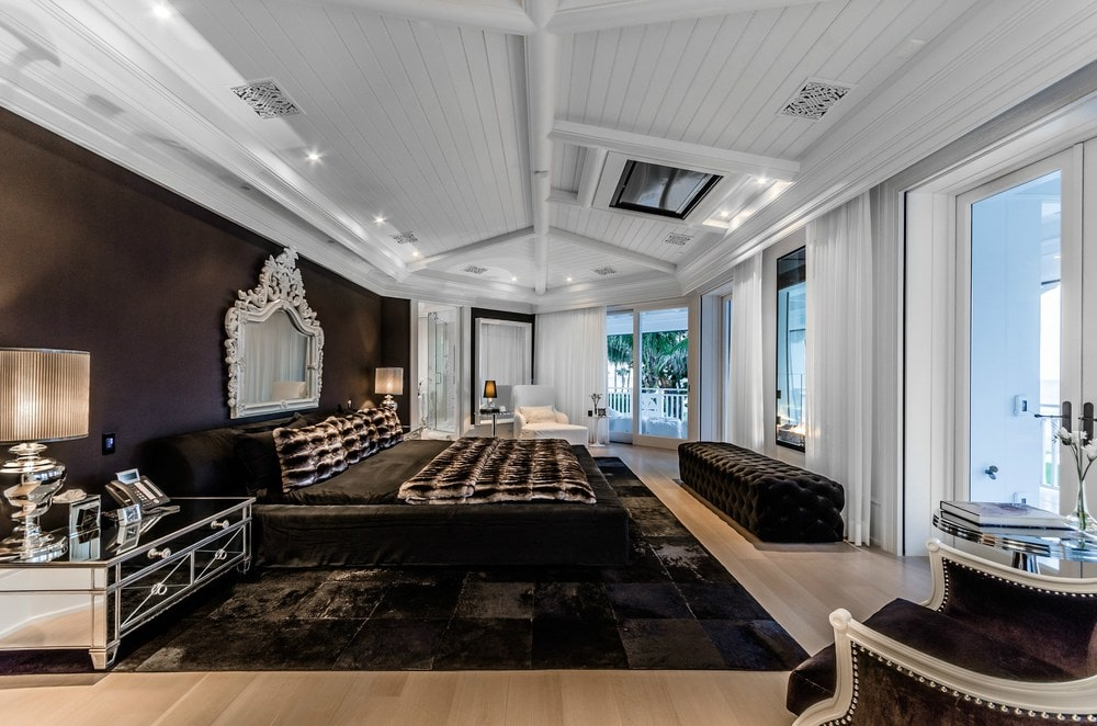 The dark tone of the large bed matches with the area rug that contrasts the light hardwood flooring but matches with the cushioned bench across from the bed. Images courtesy of Toptenrealestatedeals.com.