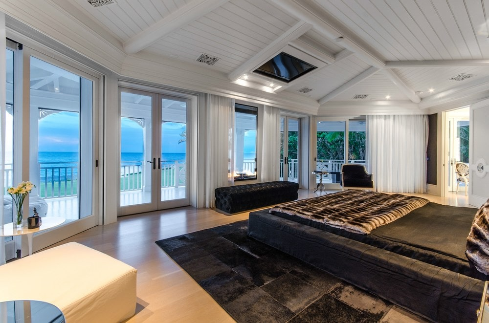 This other view of the bedroom shows the row of glass walls and glass doors opposite from the bed. These bright walls match well with the white wooden shiplap ceiling with exposed beams. Images courtesy of Toptenrealestatedeals.com.