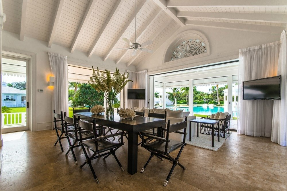 This dining area has a large dark wooden rectangular dining table topped with a simple chandelier from the tall beige arched ceiling with exposed beams. Images courtesy of Toptenrealestatedeals.com.