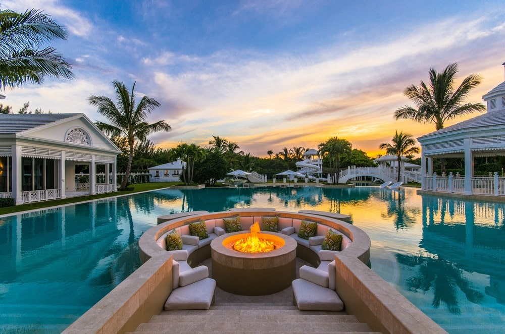 There is a lovely firepit area by the side of the pool surrounded by comfortable seats and a background of the pool. Images courtesy of Toptenrealestatedeals.com.