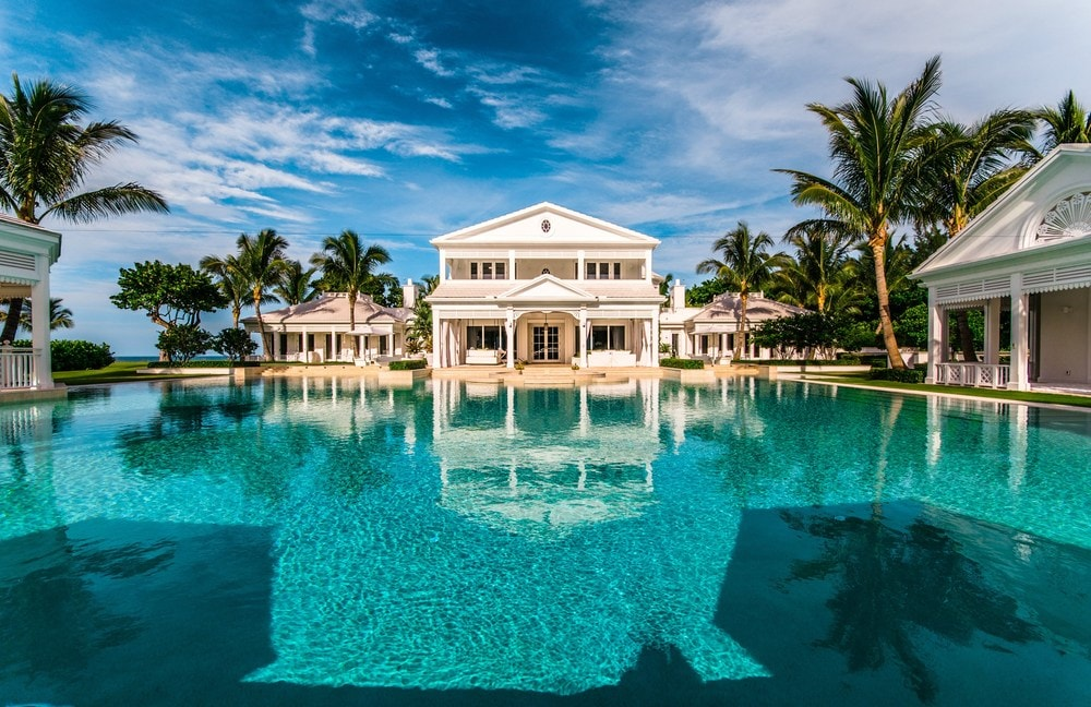 This view from the large pool shows the beautiful two-story guest house of the property with its light beige exterior reflected on the pool. Images courtesy of Toptenrealestatedeals.com.
