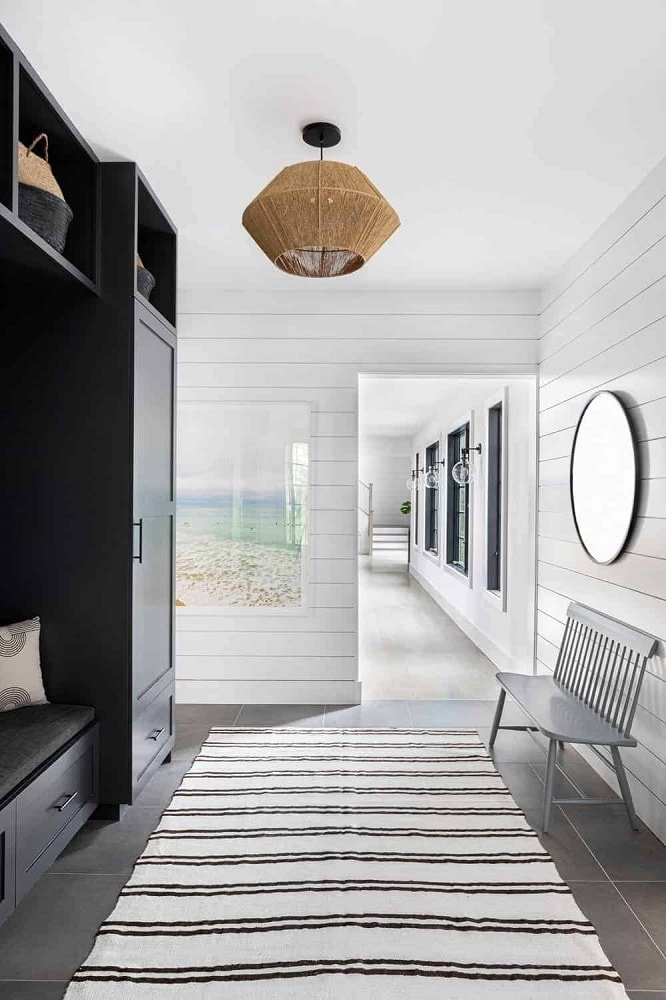 This is a charming foyer with a large black wooden mudroom on the side. It stands out against the white shiplap walls adorned with a round mirror, a painting and a rustic wooden bench. These are topped with a white ceiling that has a rustic lighting.
