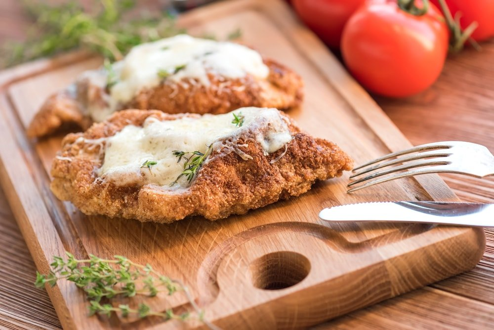 Baked chicken parmesan on a chopping board with garnish.