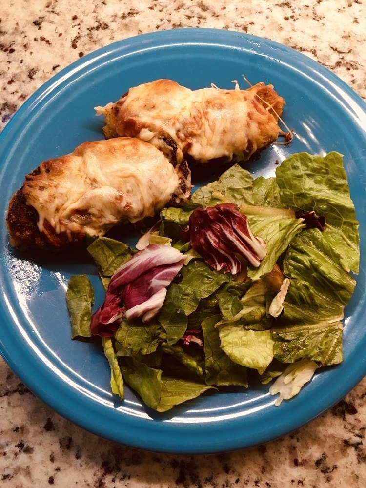 A lovely plate of baked chicken parmesan with a serving of side salad.