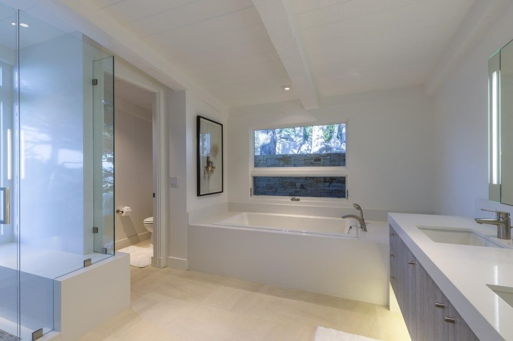 This is the primary bathroom with a large bathtub inlaid with the same beige material as the walls. This is placed on the far wall under the window. Beisde this is the floating modern vanity with lighting underneath. Images courtesy of Toptenrealestatedeals.com.