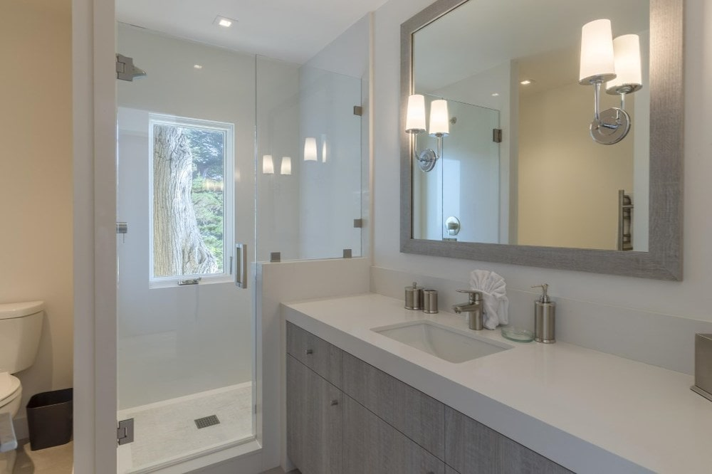 This other bathroom has a light gray vanity that matches with the frame of the mirror above that has an attached wall lamp. Next to this is the glass door of the shower area. Images courtesy of Toptenrealestatedeals.com.