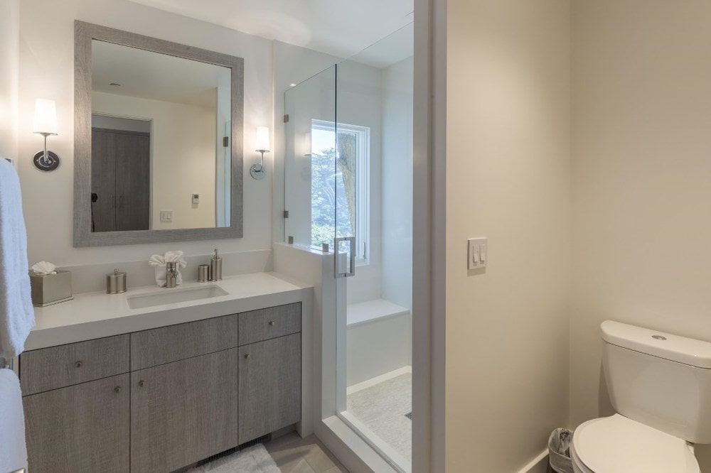 This simple bathroom has a light gray vanity with beige countertops that blend with the walls next to the glass-enclosed walk-in shower area. Images courtesy of Toptenrealestatedeals.com.