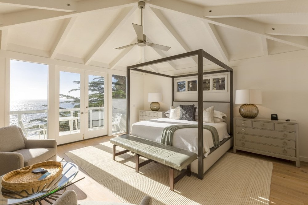 This is the primary bedroom with a dark wooden four-poster bed that stands out against the light beige walls and arched ceiling with exposed beams that hangs a ceiling fan in the middle. Images courtesy of Toptenrealestatedeals.com.