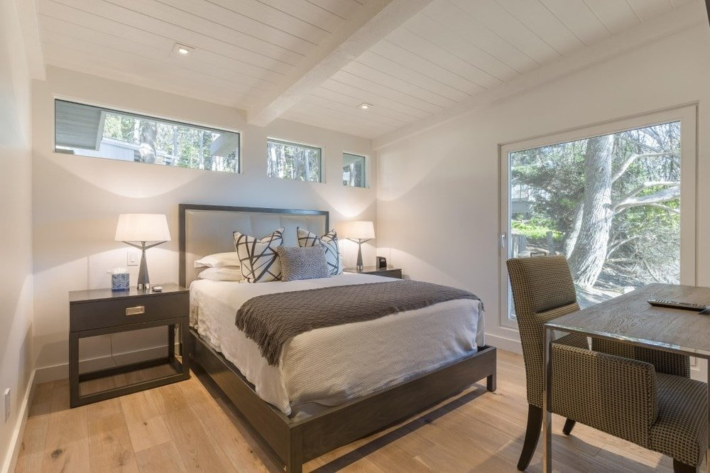 This is a cozy and homey bedroom with transom windows that bring in natural lighting for the beige shiplap ceiling with exposed beams over the comfortable bed flanked with table lamps. Images courtesy of Toptenrealestatedeals.com.