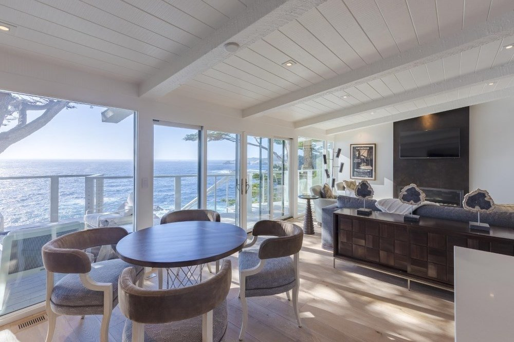 By the edge of the kitchen island is this informal dining area and breakfast nook with a small round wooden table with a clear view of the ocean through glass walls. Images courtesy of Toptenrealestatedeals.com.