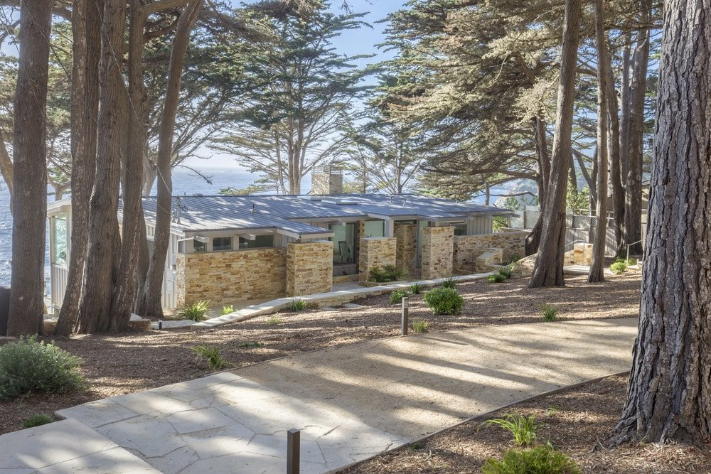 This is the front view of the house that showcases the tall trees shading the house that has textured stone exterior walls and perched on a cliff overlooking the ocean. Images courtesy of Toptenrealestatedeals.com.