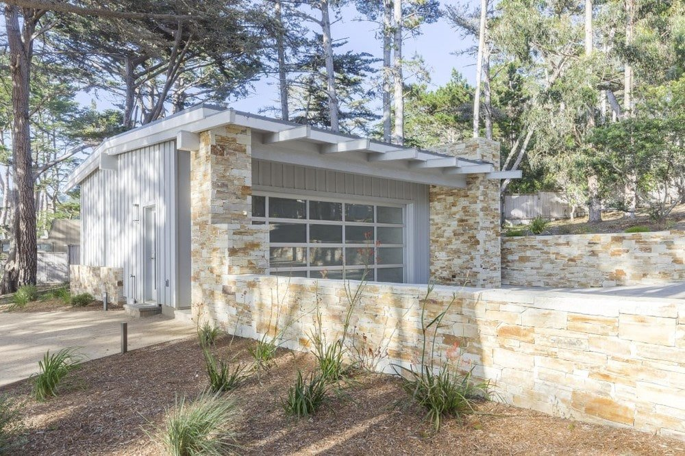 This is the charming garage of the house with textured beige stone walls to pair with the glass panels of the garage door. Images courtesy of Toptenrealestatedeals.com.