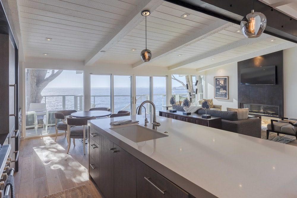 This view of the kitchen shows the beautiful beige countertop of the kitchen island that matches with the beige cathedral ceiling. The dark cabinetry of the kitchen matches with the dark exposed beam of the ceiling. Images courtesy of Toptenrealestatedeals.com.