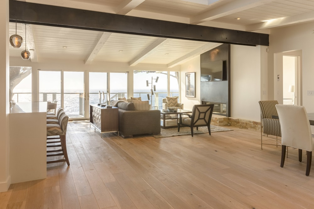 This is the spacious living room with comforatble light gray cushioned sofas to match the light tones of the beige walls and cathedral ceiling. These are then contrasted by the sleek black fireplace. Images courtesy of Toptenrealestatedeals.com.