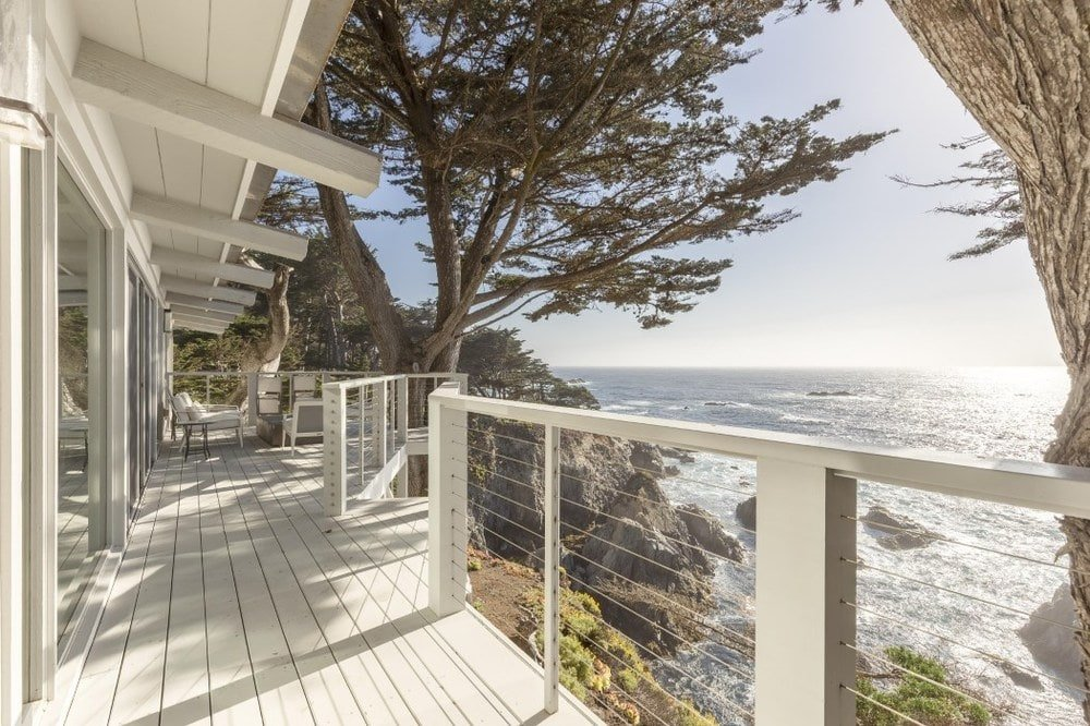 The viewing deck and patio has charming wood plank flooring with a light tone to match the exterior walls and railings complemented by the beautiful scenic ocean view. Images courtesy of Toptenrealestatedeals.com.