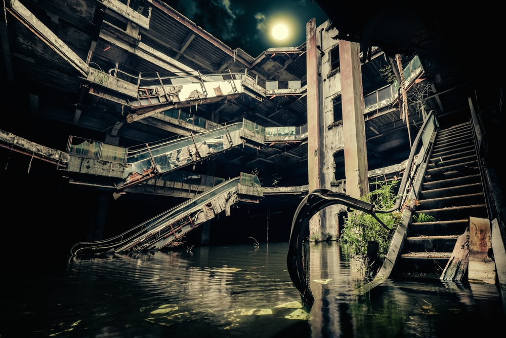 Gloomy abandoned multi-level building with damaged escalators.