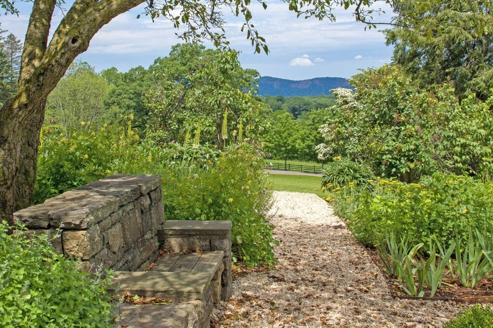 Here's a stone bench seat set on the side of the walkway along the home's garden. Images courtesy of Toptenrealestatedeals.com.